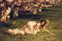Sinnliche Frau auf Gras mit Blüte stockfotografie