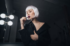 Sinnliche Frau in der blonden Perücke, die Lippenstift in der Umkleidekabine anwendet Lizenzfreies Stockfoto
