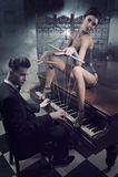 Sinnliche Frau in der reizvollen Wäsche, die auf einem Klavier sitzt Lizenzfreies Stockfoto