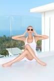 Sinnliche Frau, die am Balkon mit einer Ansicht sitzt Stockfotografie