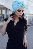 Sinnliche Frau, die eleganten schwarzen Kleider- und Seidenturban trägt Stockfotos