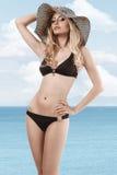 Sinnliche Frau im Bikini und im eleganten Sommerhut Lizenzfreie Stockbilder