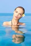 Sinnliche Frau im blauen Wasser mit Blume auf Ohr Stockbild