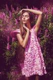 Sinnliche Frau im rosa Kleid und im Fliegen blüht Lizenzfreies Stockfoto