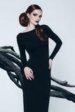 Sinnliche Frau im schwarzen Kleid und in den Bäumen Lizenzfreie Stockfotografie