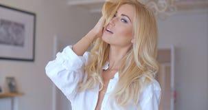 Sinnliche Frau im Weiß, das ihr Haar berührt Lizenzfreie Stockbilder