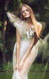 Sinnliche Frau im weißen Kleid mit Orchidee Stockbild