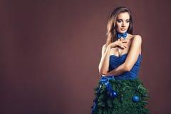 Sinnliche Frau im Weihnachtsbaumkleid auf braunem Hintergrund Stockbilder