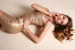 Sinnliche Frau mit dem blonden gelockten Haar im eleganten Goldkleid Stockbild