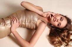 Sinnliche Frau mit dem blonden gelockten Haar im eleganten Goldkleid Stockfotos