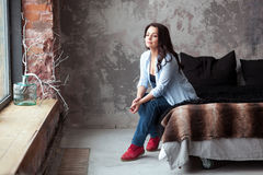 Sinnliche Frau mit dem dunklen Haar im blauen Hemd und in den Jeans, die zu Hause auf einem Bett sitzen Dachbodenartinnenraum Stockbilder