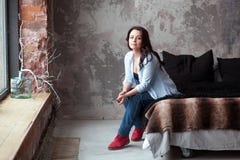 Sinnliche Frau mit dem dunklen Haar im blauen Hemd und in den Jeans, die zu Hause auf einem Bett sitzen Dachbodenartinnenraum Lizenzfreie Stockbilder