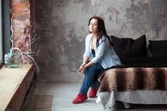 Sinnliche Frau mit dem dunklen Haar im blauen Hemd und in den Jeans, die zu Hause auf einem Bett sitzen Dachbodenartinnenraum Stockfotografie