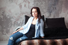 Sinnliche Frau mit dem dunklen Haar im blauen Hemd und in den Jeans, die zu Hause auf einem Bett sitzen Dachbodenartinnenraum Lizenzfreies Stockfoto