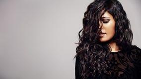 Sinnliche Frau mit dem glänzenden gelockten Haar stockfotografie