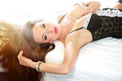 Sinnliche Frau mit dem langen braunen Haar, das auf Bett liegt Lizenzfreie Stockfotos