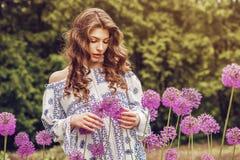 Sinnliche Frau mit dem langen Haar unter purpurroten Blumen Stockbilder