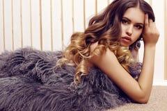 Sinnliche Frau mit dem luxuriösen gelockten Haar, das eleganten Pelzmantel trägt Stockfotografie
