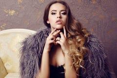 Sinnliche Frau mit dem luxuriösen gelockten Haar, das eleganten Pelzmantel trägt Lizenzfreie Stockfotos