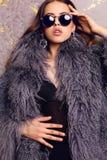 Sinnliche Frau mit dem luxuriösen gelockten Haar, das eleganten Pelzmantel trägt Stockbilder