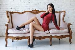 Sinnliche Frau mit dem perfekten Körper, der in einem roten kurzen Kleid aufwirft Stockfotografie