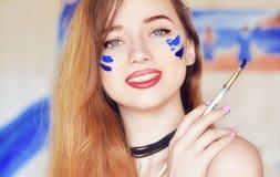 Sinnliche Frau mit Farbe auf dem Gesicht Mädchen, das einen Malerpinsel mit blauer Farbe hält Mädchenlächeln, glücklich Stockfoto