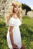 Sinnliche Frau mit langem blondes Haar- und Blumenstirnband Stockfotos