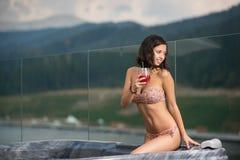 Sinnliche Frau mit perfektem Körper im Bikini, der am Jacuzzi mit Cocktail sitzt und weg schaut Stockfotos