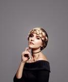 Sinnliche Frau mit perfekter Haut und umsponnener Frisur Stockfotografie