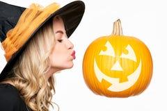 ` Sinnliche Halloween-Hexen-küssende Jacks O Laterne Attraktive junge Frau kleidete im Hexenkostüm und in großem Halloween-Kürbis lizenzfreie stockfotos