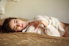 Sinnliche junge Frau, die durchdacht zu Hause auf dem Bett liegt Lizenzfreie Stockfotos