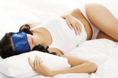 Sinnliche junge Frau, die im Bett schläft Lizenzfreie Stockbilder
