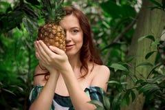 Sinnliche junge Frau mit einer Ananas am tropischen Wald Lizenzfreie Stockbilder