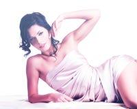 Sinnliche junge Frau mit schönem Körper in der beige Seide Lizenzfreie Stockfotografie