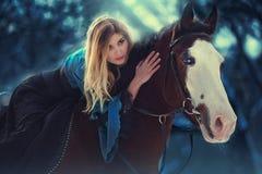 Sinnliche junge Schönheit, die ein Pferd reitet Stockfoto
