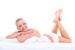Sinnliche lächelnde Frau, die auf dem Bett liegt Stockfotos