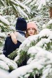 Sinnliche Paare unter Tannenbäumen im Schnee Lizenzfreie Stockfotografie