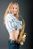 Sinnliche reizvolle Blondine der Junge recht mit Saxophon stockbilder