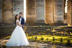Sinnliche romantische Jungvermähltenbraut und -bräutigam, die vor alter barocker Kirche umarmt stockfotos
