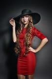 Sinnliche schöne Frau im roten Kleid und im Hut Stockbild