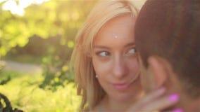Sinnliche schöne träumerische junge blonde Braut und hübscher Bräutigam bei Sonnenuntergang in der Parknahaufnahme stock video footage