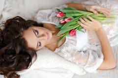 Sinnliche schöne und reizend Brunettefrau, die auf Bett und s liegt Lizenzfreies Stockbild