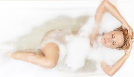 Sinnliche und sexy kaukasische blonde Frau in der schäumenden Badewanne während der Körper-Behandlung Lizenzfreies Stockfoto