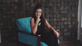 Sinnliche wehmütige Brunettefrau, die das Sitzen im Lehnsessel aufwirft stock video footage