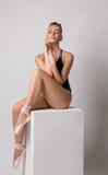 Sinnlicher Balletttänzer, der das Sitzen auf Würfel aufwirft Lizenzfreie Stockfotografie
