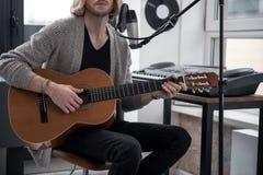 Sinnlicher junger Mann, der Gitarre hält Stockfotos