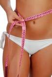Sinnlicher weiblicher Körper mit Bikini und Maßband Lizenzfreie Stockfotos