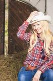 Sinnliches blondes Cowgirl, das innerhalb des Gutshauses lächelt vertikal Lizenzfreies Stockbild
