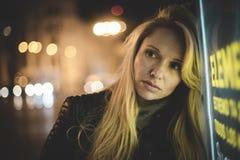 Sinnliches blondes in der Stadt nachts, mit Neonlichtern und einem Zeichen Lizenzfreie Stockfotos