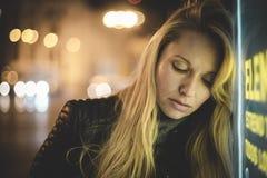 Sinnliches blondes in der Stadt nachts, mit Neonlichtern und einem Zeichen Lizenzfreies Stockbild